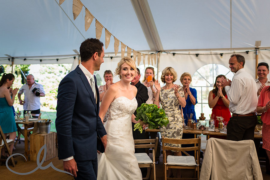 bride and groom enter the marquee for their wedding breakfast