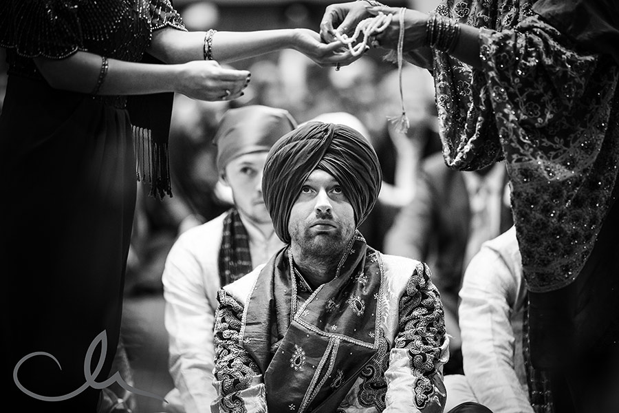 the broach is removed from the groom at Rukmanie-and-David's-Sikh-Wedding-Photography