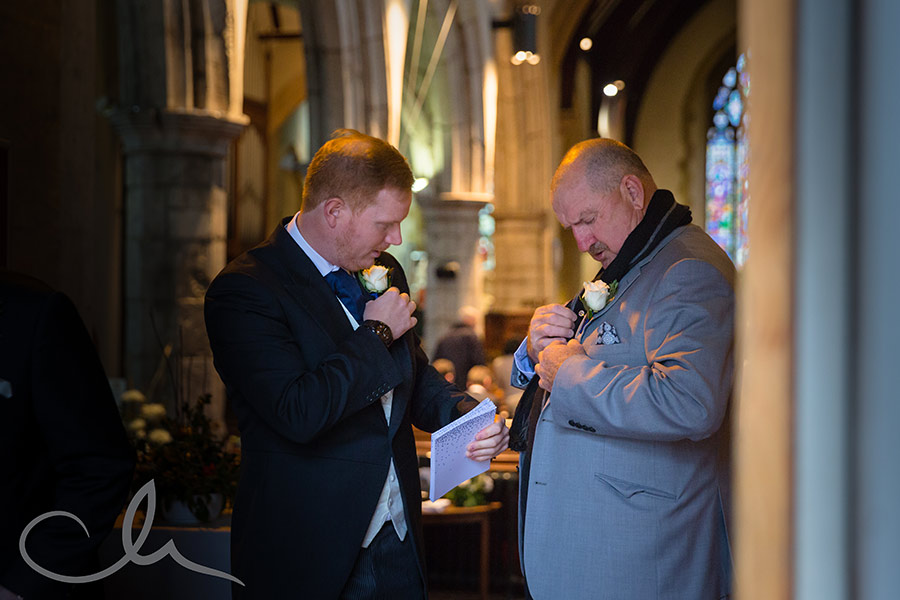 Usher helps a guest with their corsage at Sarah & Dan's Chilham-Church-Wedding