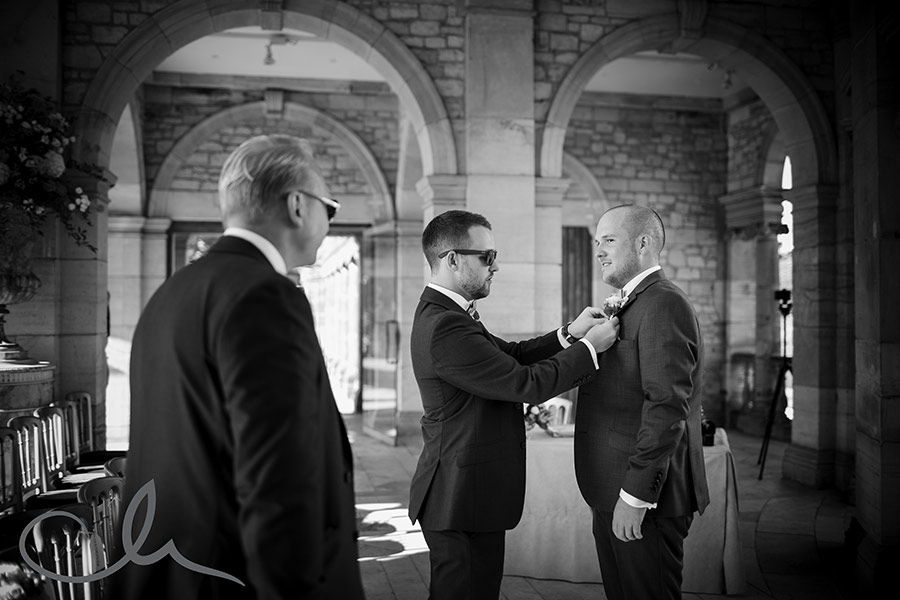 Best man helps the groom with his corsage at his Hever Castle Wedding