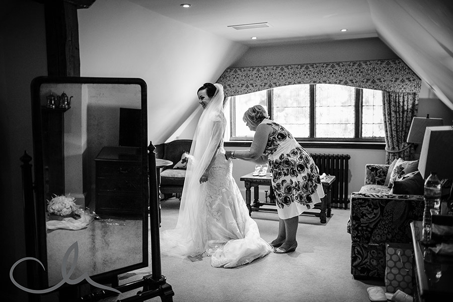 brides mother helps her daughter with her wedding dress at ther Hever Castle Wedding