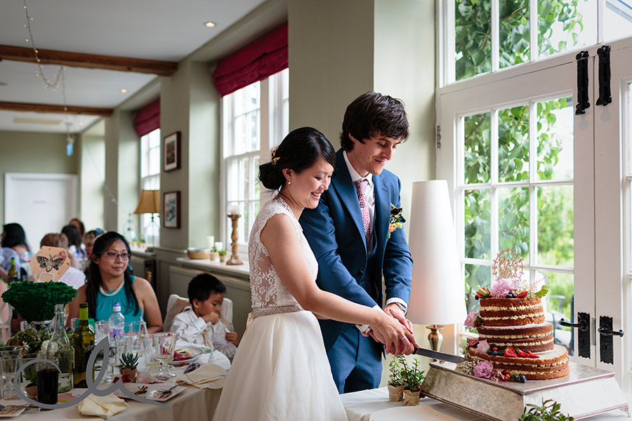 The bride and groom cut their wedding cake at their Secret Garden Wedding