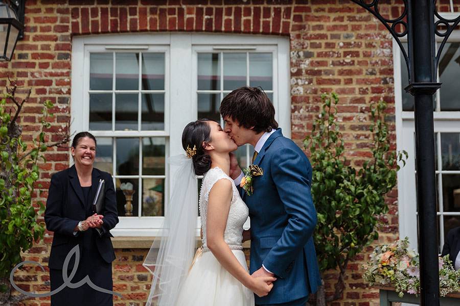 the bride and groom have their first kiss at their Secret Garden Wedding in Kent