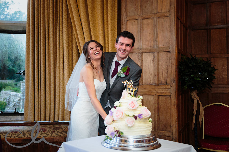 Bride and groom cut their wedding cake at Lympne Castle Kent Wedding Venue