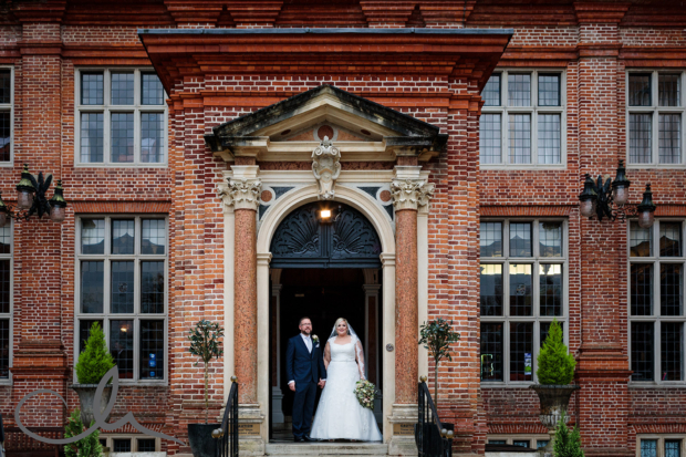 Newly weds have their portrait taken in front of Broome Park Wedding Venue Kent