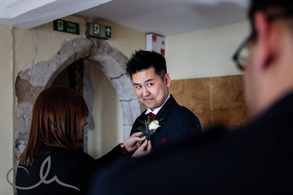 the best man has his corsage attached at Lympne Castle