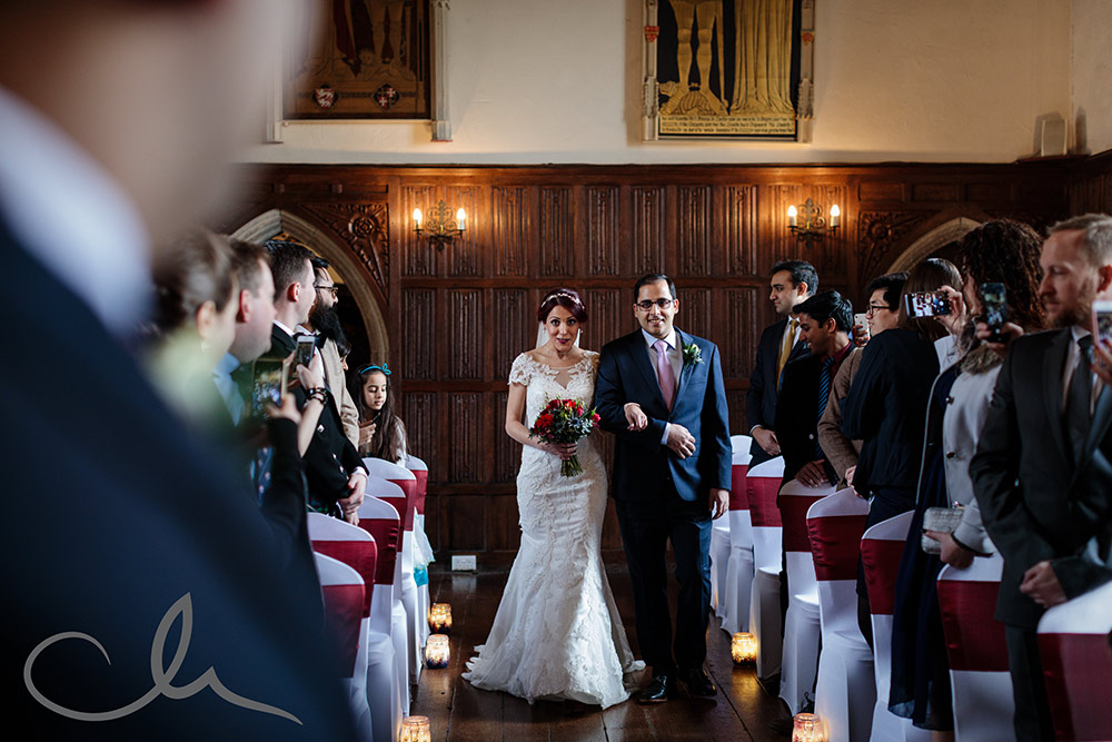 The bride and her brother walk up the aisle to meet her future husband at Lympne Castle