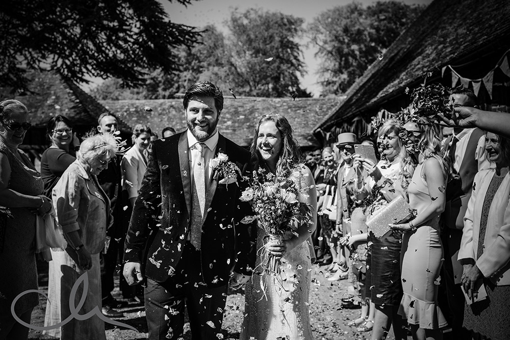 newlywed couple are showered with confetti